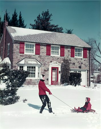 1950s WOMAN MOTHER PULLING GIRL DAUGHTER ON SLED IN SNOW IN FRONT OF SUBURBAN STONE HOUSE Stock Photo - Rights-Managed, Code: 846-02795241