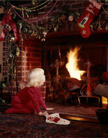 1960s SMALL BLOND GIRL AT FIREPLACE DECORATED FOR CHRISTMAS HOLDING STOCKING LOOKING FOR SANTA CLAUS Stock Photo - Rights-Managed, Code: 846-02795254