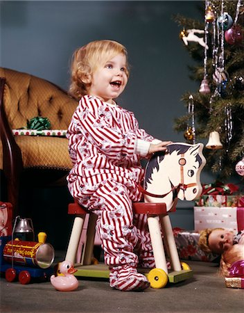 1960s TODDLER GIRL ON WHEELED TOY RIDING HORSE NEAR CHRISTMAS TREE LIVING ROOM HAPPY SMILING Stock Photo - Rights-Managed, Code: 846-02795256