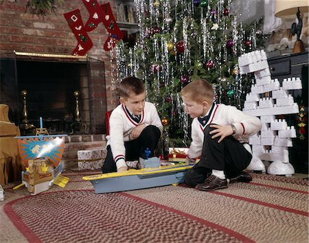 1960s TWO BROTHERS PLAYING WITH TOY MODEL AIRCRAFT CARRIER AND LEGO BLOCKS BY DECORATED CHRISTMAS TREE Stock Photo - Rights-Managed, Code: 846-02795261