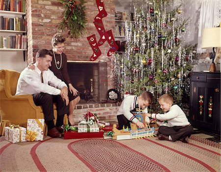 pantyhose kid - 1960s FAMILY IN LIVING ROOM CHRISTMAS TREE BOYS PLAYING WITH TOYS MOTHER FATHER SITTING IN CHAIR Stock Photo - Rights-Managed, Code: 846-02795263