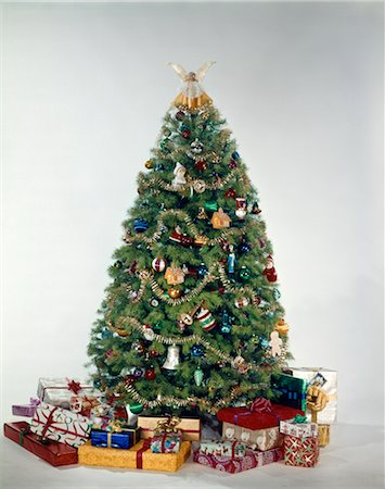 1950s 1960s 1970'S COLORFUL DECORATED CHRISTMAS TREE SURROUNDED BY PRESENTS STUDIO INDOOR Stock Photo - Rights-Managed, Code: 846-02795279