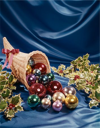1960s STILL LIFE CORNUCOPIA FILLED HOLLY MULTI-COLORED CHRISTMAS BALLS DECORATIONS ON BLUE VELVET Stock Photo - Rights-Managed, Code: 846-02795270