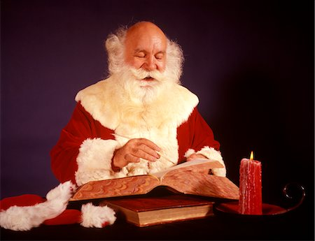 1950s 1960s 1970s BALD SANTA CLAUS WRITING LIST IN BIG BOOK BY CANDLE LIGHT STUDIO INDOOR Stock Photo - Rights-Managed, Code: 846-02795285