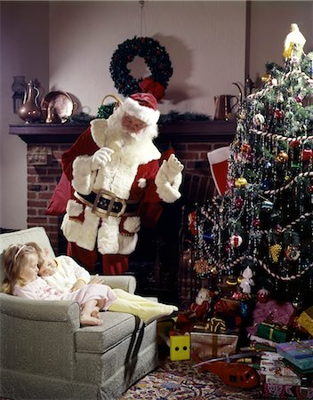 1960s SANTA CLAUS IN LIVING ROOM NEAR CHRISTMAS TREE WAVING TO BOY AND GIRL SLEEPING IN CHAIR Stock Photo - Rights-Managed, Code: 846-02795290