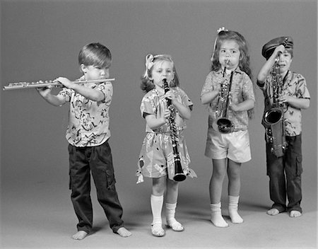 TWO BOYS AND TWO GIRLS PLAYING FLUTE CLARINET TRUMPET AND SAXOPHONE INDOOR Stock Photo - Rights-Managed, Code: 846-02795399