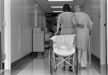 rehabilitation - 1980s REAR VIEW OF WOMAN WITH ARM AROUND ELDERLY MAN USING WALKER WHEELCHAIR BEHIND THEM Stock Photo - Rights-Managed, Code: 846-02795390
