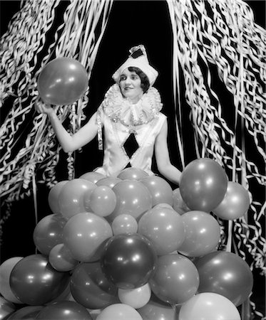 1920s 1930s SMILING YOUNG WOMAN Pierrot CLOWN AMID PARTY BALLOONS AND PAPER STREAMERS Stock Photo - Rights-Managed, Code: 846-02795476