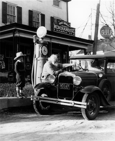 ELDERLY GRANDFATHER FILLING UP FORD CAR IN FRONT OF PENNSYLVANIA GENERAL STORE WITH GRANDSON WATCHING 1930s Stock Photo - Rights-Managed, Code: 846-02795507
