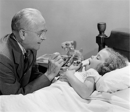 1950s LITTLE GIRL SICK IN BED STICKING OUT HER TONGUE DOCTOR ON AT HOUSE CALL AT BED SIDE LOOKING AT HER THROAT Stock Photo - Rights-Managed, Code: 846-02795514