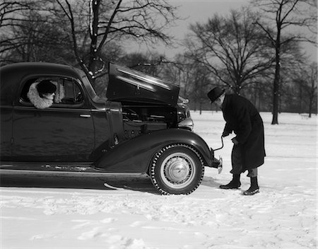 stalled car - 1930s 1940s WOMAN PASSENGER WATCHING MAN MOTORIST TRY TO CRANK START A CHEVROLET COUPE STALLED IN SNOW Stock Photo - Rights-Managed, Code: 846-02795516