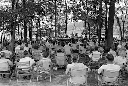 sitting under tree - 1950s CROWD GROUP MEN WOMEN SIT FOLDING CHAIRS UNDER SHADE TREES LISTENING SUMMER BAND CONCERT SMALL TOWN Stock Photo - Rights-Managed, Code: 846-02795511