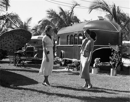 1930s 2 WOMEN STANDING TALKING ON TROPICAL LAWN IN FLORIDA TRAILER PARK WITH A CAR UMBRELLA & CHAIRS Stock Photo - Rights-Managed, Code: 846-02795530