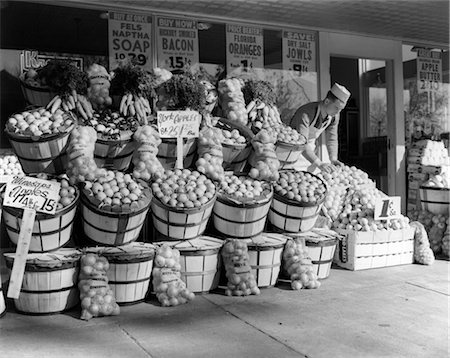 1940s GROCER IN WHITE CAP & APRON SETTING OUT FRUIT ON SIDEWALK IN FRONT OF GROCERY STORE Stock Photo - Rights-Managed, Code: 846-02795627