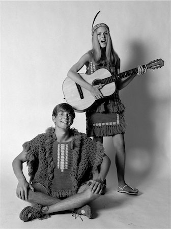 1960s 1970s TEENAGE COUPLE DRESSED IN CROCHETED CLOTHES WOMAN WITH FEATHER HEADBAND PLAYING GUITAR MAN SINGING Stock Photo - Rights-Managed, Code: 846-02795645