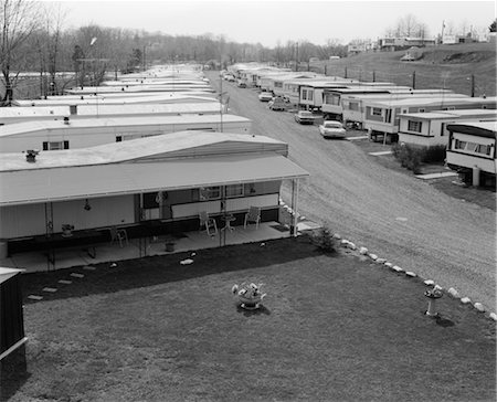1970s TRAILER PARK WITH ROWS OF MOBILE HOMES ON EITHER SIDE OF GRAVEL ROAD Stock Photo - Rights-Managed, Code: 846-02795646