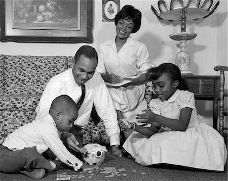 1960s AFRICAN AMERICAN FAMILY ON LIVING ROOM FLOOR COUNTING CHANGE IN PIGGY BANK Stock Photo - Rights-Managed, Code: 846-02795691