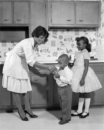 1960s SMILING AFRICAN AMERICAN WOMAN MOTHER IN APRON AND PUMPS GIVING A GLASS OF MILK TO SON AND DAUGHTER WITH MARY JANE SHOES Stock Photo - Rights-Managed, Code: 846-02795692