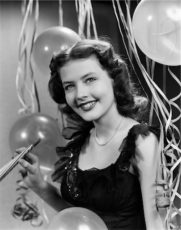 1940s 1950s SMILING WOMAN BLACK PARTY DRESS PEARLS HOLDING NEW YEAR PARTY NOISE MAKER STREAMERS BALLOONS BACKGROUND Stock Photo - Rights-Managed, Code: 846-02795715