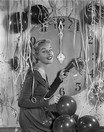 1950s GLAMOROUS WOMAN HOLDING PARTY NOISE MAKER BALLOONS CONFETTI STREAMERS CLOCK AT MIDNIGHT BEHIND HER Stock Photo - Rights-Managed, Code: 846-02795742