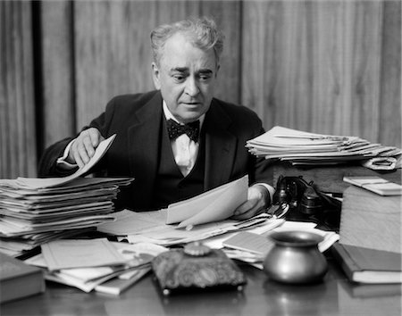 people in panic - 1920s 1930s ELDERLY EXECUTIVE MAN SITTING AT DESK LOOKING THROUGH PAPERS Stock Photo - Rights-Managed, Code: 846-02795756