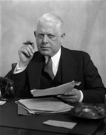 1930s MAN IN OFFICE SITTING AT DESK HOLDING PAPERS SMOKING A CIGAR Stock Photo - Rights-Managed, Code: 846-02795762
