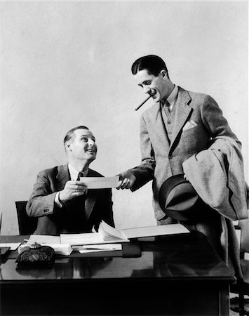 1930s TWO MEN AT DESK IN OFFICE ONE MAN WITH CIGAR EXCHANGING PAPER WITH OFFICE WORKER Stock Photo - Rights-Managed, Code: 846-02795783