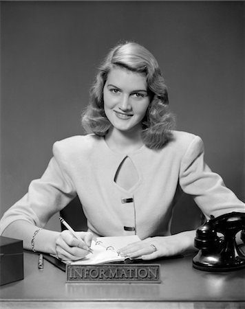 secretary desk - 1950s WOMAN SITTING AT INFORMATION DESK IN OFFICE WRITING IN APPOINTMENT BOOK Stock Photo - Rights-Managed, Code: 846-02795835
