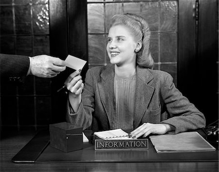 secretary desk - 1940s YOUNG SMILING WOMAN APPOINTMENT SECRETARY RECEPTIONIST ACCEPTING BUSINESS CARD FROM MAN'S HAND Stock Photo - Rights-Managed, Code: 846-02795854