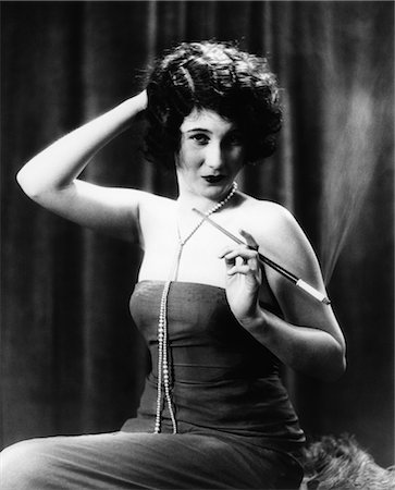 1920s WOMAN WEARING STRAPLESS GOWN AND STRING OF PEARLS HOLDING LONG CIGARETTE HOLDER WITH OTHER HAND ON BACK OF HEAD Stock Photo - Rights-Managed, Code: 846-02795866