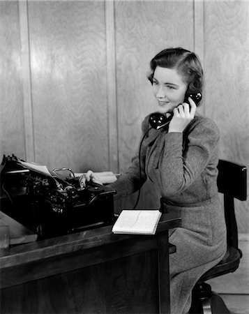 secretary desk - 1940s SMILING YOUNG WOMAN SECRETARY RECEPTIONIST SITTING AT OFFICE DESK TALKING ON TELEPHONE Stock Photo - Rights-Managed, Code: 846-02795949