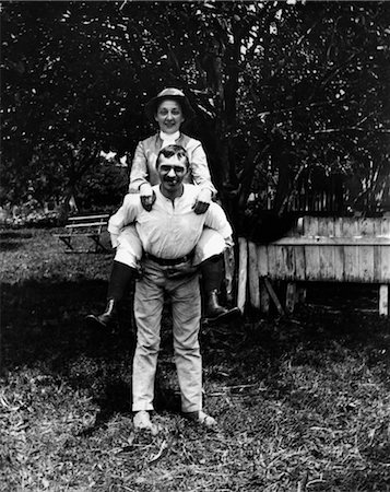 TURN OF THE CENTURY MAN SMOKING CIGAR CARRYING WIFE PIGGYBACK Stock Photo - Rights-Managed, Code: 846-02795982