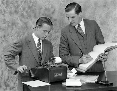 1930s CLERK AND YOUNG ASSISTANT IN OFFICE USING LEDGER BOOK & ADDING MACHINE Stock Photo - Rights-Managed, Code: 846-02796028