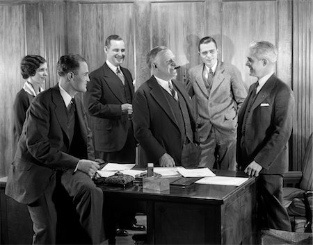 1930s SMILING OFFICE GROUP FOUR MEN ONE WOMAN BOSS SMOKING CIGAR TALKING MEETING FIFTH MAN Stock Photo - Rights-Managed, Code: 846-02796094