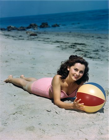 1940s 1950s BRUNETTE WOMAN LYING ON BEACH HOLDING BEACH BALL Stock Photo - Rights-Managed, Code: 846-02796102
