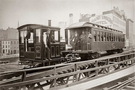 1880s LOCOMOTIVE & ONE PASSENGER CAR RUNNING ON EAST 42nd STREET GROUP OF MEN ON BOARD GRAND UNION HOTEL IN BACKGROUND Stock Photo - Rights-Managed, Code: 846-02796326