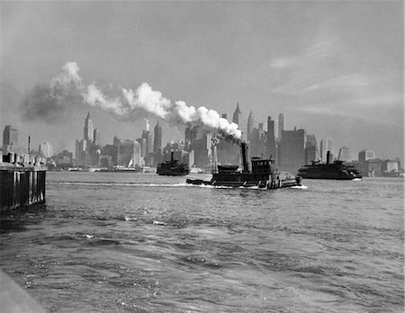 1930s 1933 RETRO STEAM ENGINE TUG BOAT AND STATEN ISLAND FERRY BOATS ON HUDSON RIVER AGAINST MANHATTAN ISLAND SKYLINE NEW YORK CITY USA Stock Photo - Rights-Managed, Code: 846-02796368
