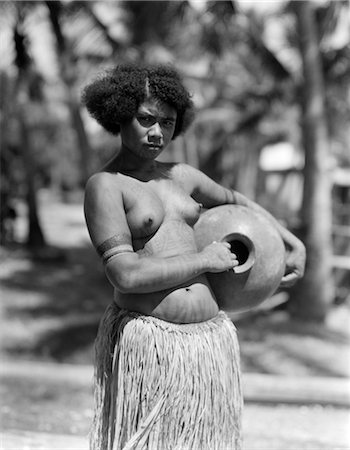 1920s 1930s SERIOUS UNSMILING PORTRAIT TOPLESS PAPUAN GIRL NATIVE IN GRASS SKIRT NEW GUINEA Stock Photo - Rights-Managed, Code: 846-02796390