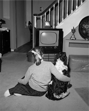 1950s BACK VIEW OF TEENAGE GIRL IN PONYTAIL WATCHING TV WITH HER DOG IN LIVING ROOM Stock Photo - Rights-Managed, Code: 846-02796550