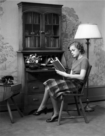 secretary desk - 1930s 1940s YOUNG WOMAN TEENAGE SITTING IN A CHAIR READING A BOOK BY A MAPLE WOOD SECRETARY DESK IN PEACEFUL HOME LIVING ROOM Stock Photo - Rights-Managed, Code: 846-02796551
