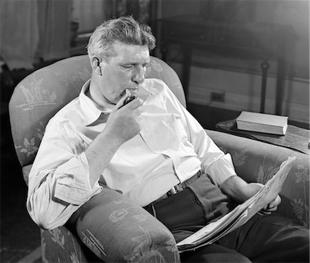 1930s MAN SITTING CHAIR READING NEWSPAPER SMOKING PIPE Stock Photo - Rights-Managed, Code: 846-02796575