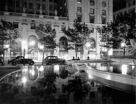 1930s NIGHT SCENE 5TH AVENUE HOTEL FRONT TREE LINED SIDEWALK MOTORCARS POOL AND PEDESTRIANS STREET LAMPS REFLECTING ON SURFACES Stock Photo - Rights-Managed, Code: 846-02796587