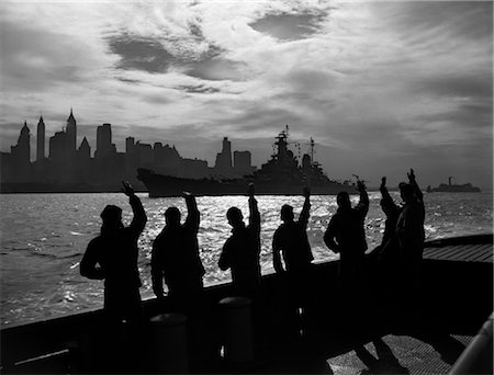 1950s SILHOUETTED SAILORS DECK OF SHIP WAVING SALUTE TO PASSING USN BATTLESHIP AT NIGHT AGAINST NEW YORK CITY SKYLINE Stock Photo - Rights-Managed, Code: 846-02796595
