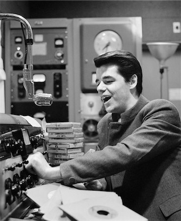 1960s SIDE VIEW OF RADIO DISC JOCKEY IN STUDIO ANNOUNCING Stock Photo - Rights-Managed, Code: 846-02796632