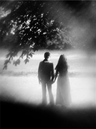 silhouette black and white - 1970s REAR VIEW SOFT-FOCUS SHOT OF COUPLE STANDING UNDER TREE HOLDING HANDS Stock Photo - Rights-Managed, Code: 846-02796641