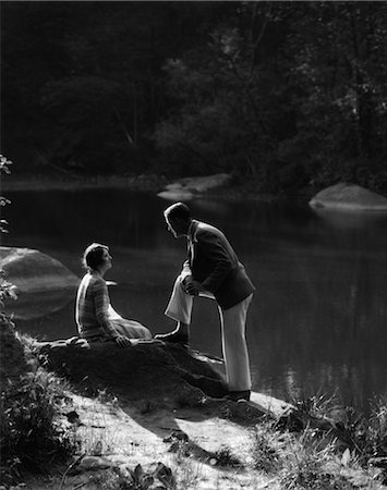 silhouette black and white - 1920s 1930s WOMAN SITTING ON ROCK LAKESIDE TALKING TO MAN STANDING WITH FOOT ON ROCK LEANING ON KNEE LISTENING Stock Photo - Rights-Managed, Code: 846-02796687