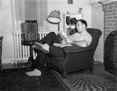 1950s MAN SITTING IN CHAIR IN LIVING ROOM SMOKING PIPE READING PAPER LISTENING TO RADIO Stock Photo - Rights-Managed, Code: 846-02796719