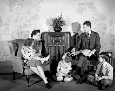1940s FAMILY MAN FATHER WOMAN MOTHER BOY SON TWO GIRLS DAUGHTERS SITTING TOGETHER LISTENING TO RADIO Stock Photo - Rights-Managed, Code: 846-02796720