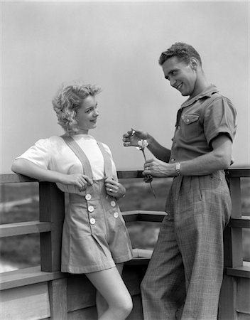 simsearch:846-02793283,k - 1940s COUPLE ON DECK WITH MAN PLUCKING PETALS FROM DAISY LIKE SHE LOVES ME... SHE LOVES ME NOT Stock Photo - Rights-Managed, Code: 846-02796736
