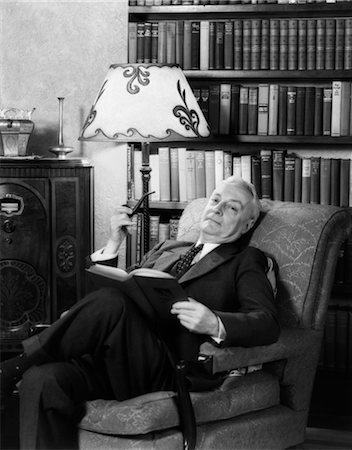 1930s ELDERLY MAN IN ARMCHAIR RELAXING WITH BOOK & PIPE & LISTENING TO RADIO Stock Photo - Rights-Managed, Code: 846-02796739